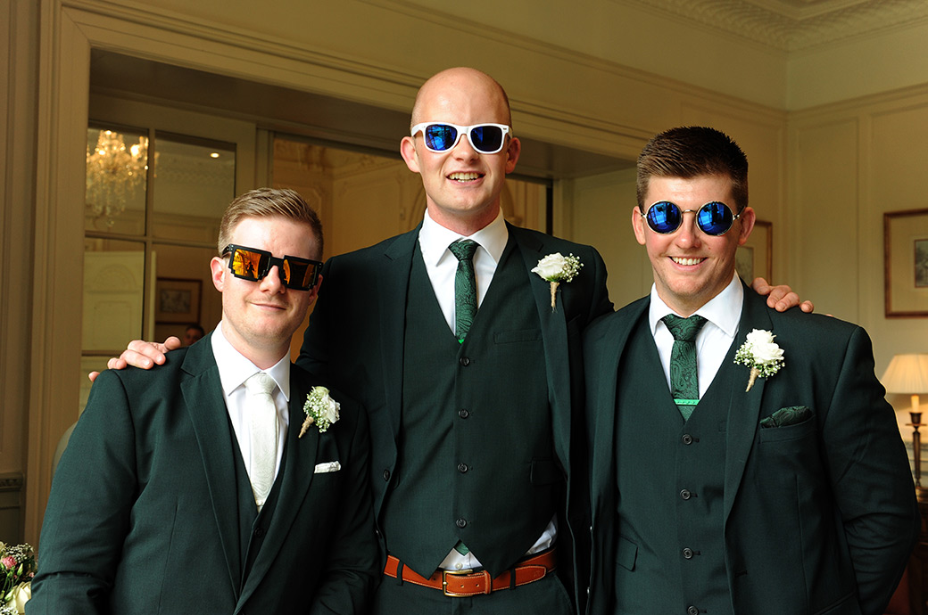 Groom and best men dressed in green and sporting some rather wacky fancy dress sunglasses at Warren House in Kingston Surrey before greeting the wedding guests