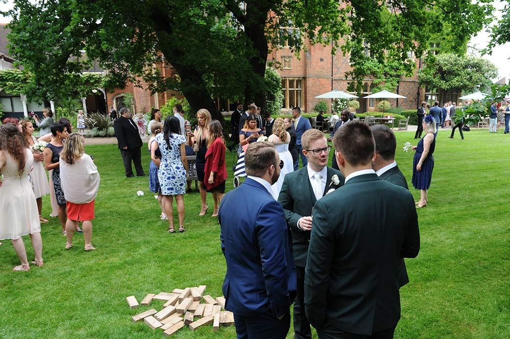 Wedding guests spread out over the lawn as they chat and drink during the reception at the tranquil and relaxed Surrey wedding venue Warren House in Kingston