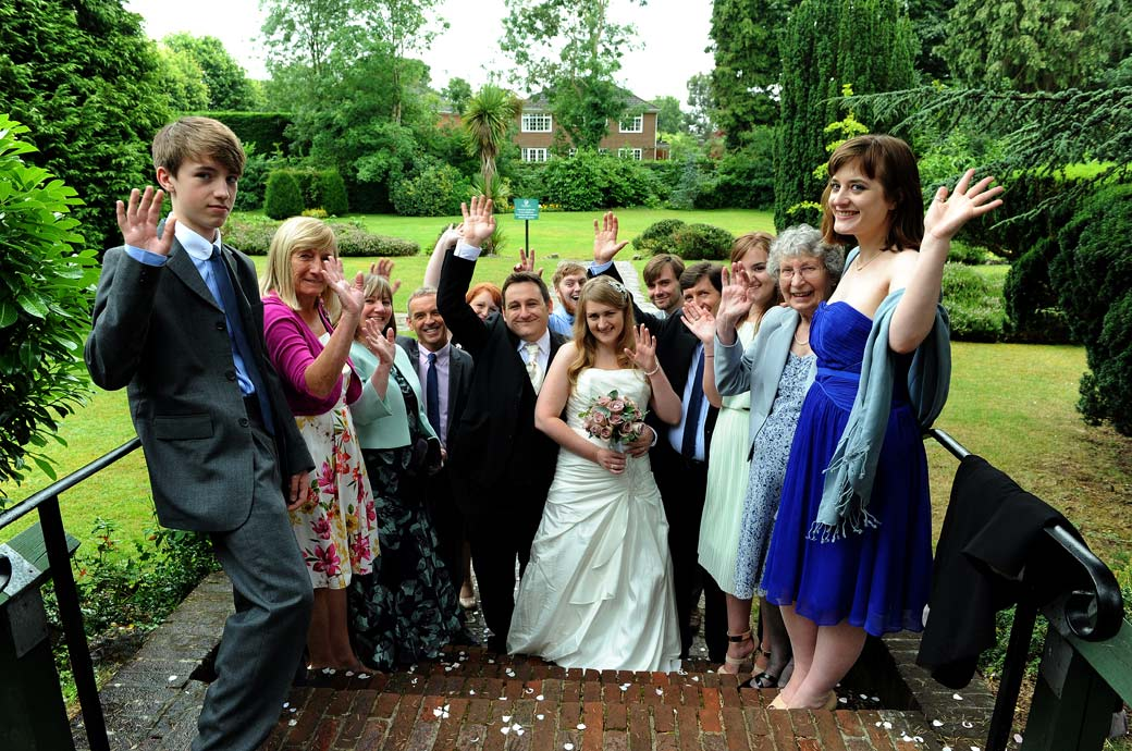 Everyone in this group wedding photograph captured waving at the Surrey Lane wedding photographer on the steps in the garden at Weybridge Register Office
