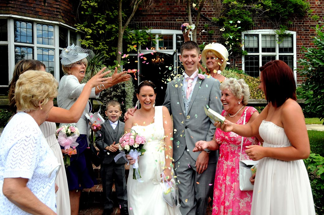 Bride and Groom laughing during the confetti throwing wedding picture taken on the steps of the garden at a Weybridge Register Office wedding