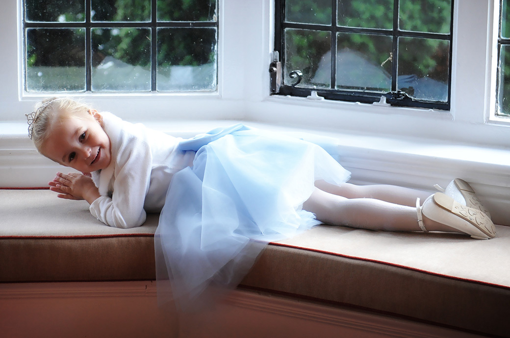 Wedding photo of a pretty little Bridesmaid at Surrey wedding venue Weybridge Register Office having fun as she stretches out on the Rylston Suite alcove window settee