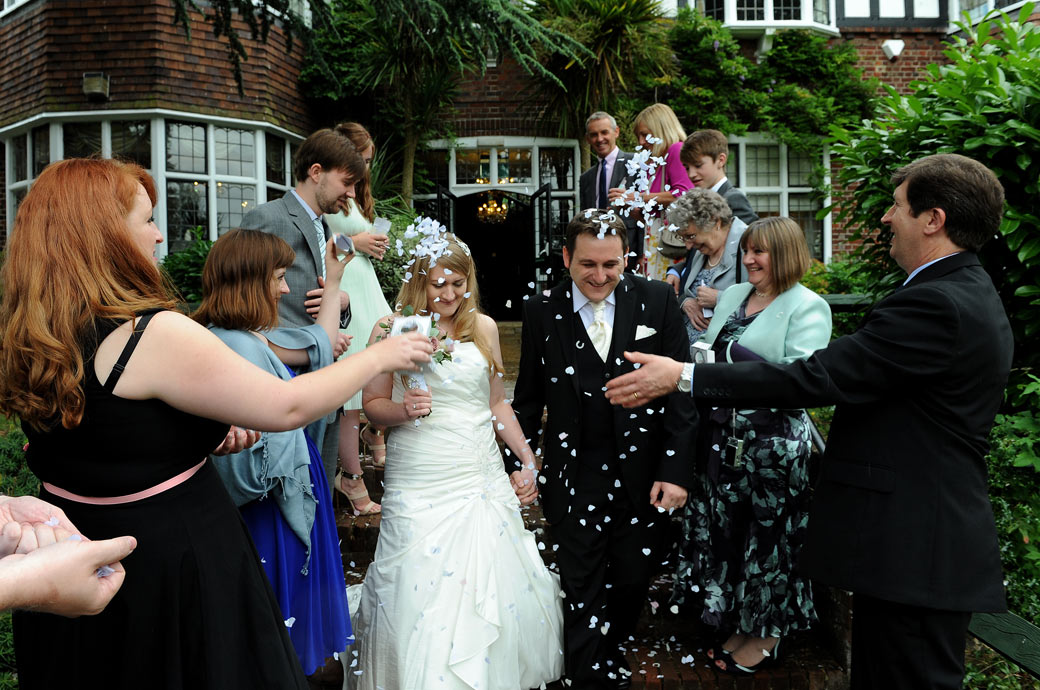 Lots of confetti time fun for the newlywed couple as they walk down the steps outside the Ryston Suite at Surrey wedding venue Weybridge Register Office