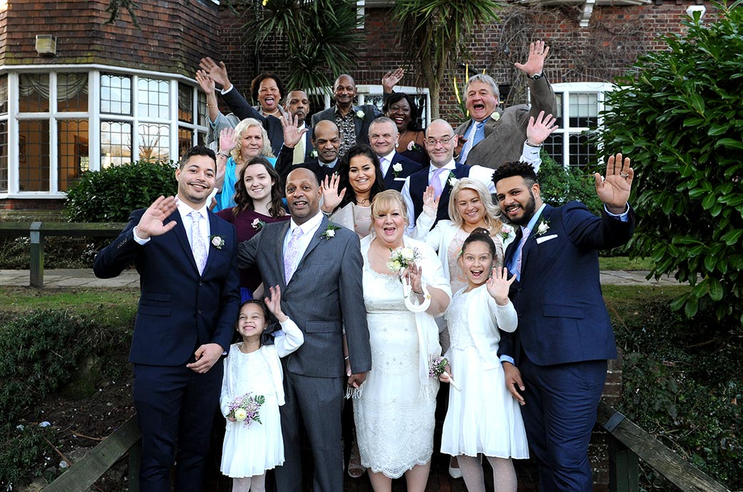 Lots of smiles and waving hands as the Bride and groom with their family and guests at Surrey wedding venue Weybridge Register Office pose on the garden steps