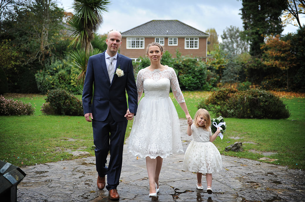 Proud and happy Bride and groom walking down the garden path of the Weybridge Register Office in Surrey hand in hand with their sweet little daughter