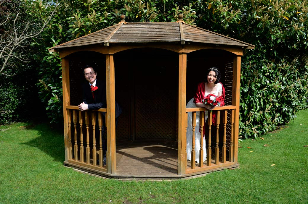 Relaxed and fun wedding photo of the newly-weds leaning out of the summerhouse in the garden at Surrey wedding venue Weybridge Register Office
