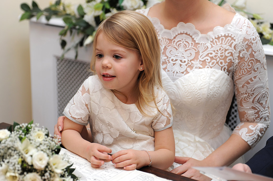 Daughter of the Bride in the Rylston Suite at Weybridge Register Office Surrey captured sitting on her mum's knee during the signing of the marriage register