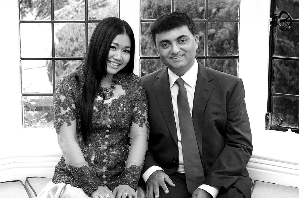Newlyweds happy loving look wedding picture captured at Surrey wedding venue Weybridge Register Office as they sit on the stone garden seat