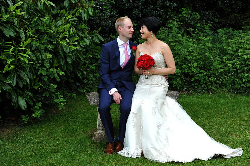 Love is in the air as a bride and groom photographed at Surrey wedding venue Weybridge Register Office sit on an old stone bench and look into each other's eyes