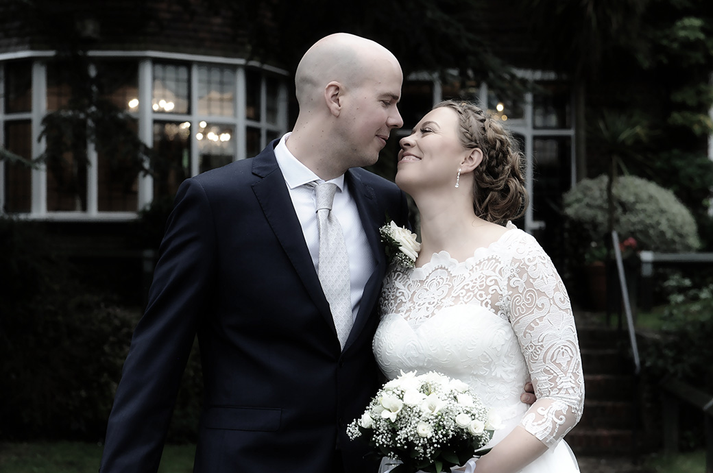 A wedding picture of loving looks exchanged in the garden after the Bride and groom are married in the Rylston Suite in Surrey at Weybridge Register Office