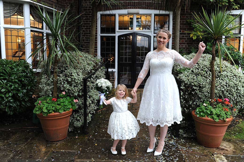 Mother Bride at Surrey wedding venue Weybridge Register Office celebrates her marriage with her pretty little daughter outside the Rylston Suite