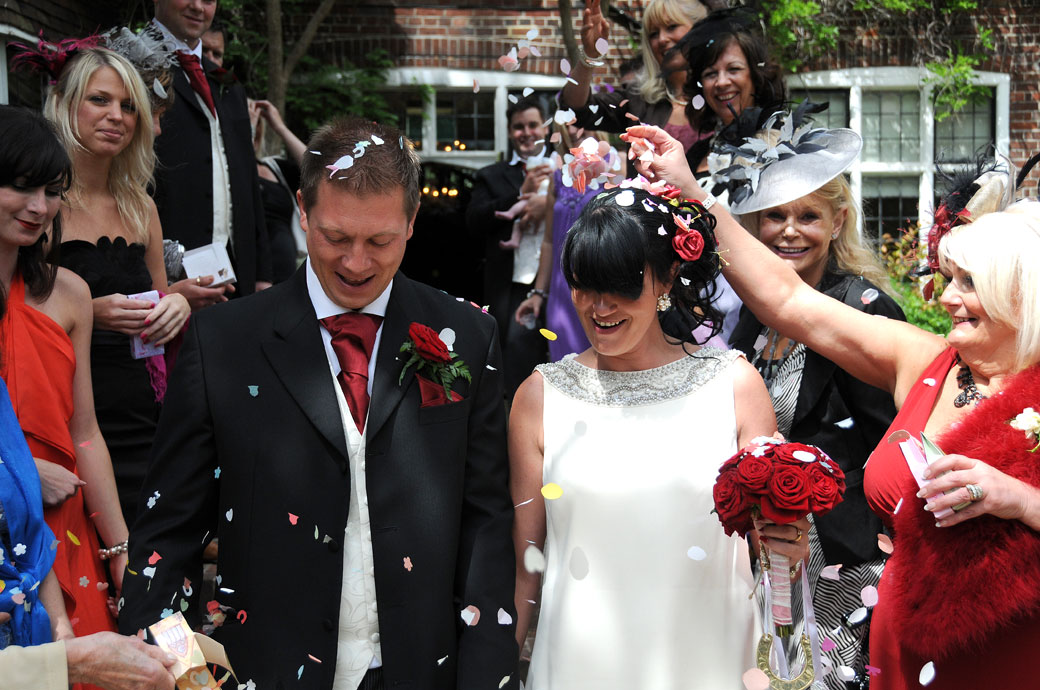Close up wedding picture of newly-weds getting covered in confetti taken on the steps of the Surrey wedding venue Weybridge Register Office