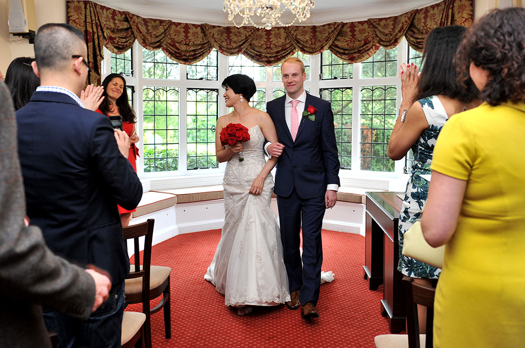 Proud smiling Groom in the Rylston Suite at Weybridge Register Office Surrey with his arm in his Bride's leads the way down the aisle to much applause