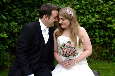 Excited groom shares a fun intimate moment with his lovely Bride as they sit on a garden bench at the relaxed Surrey wedding venue Weybridge Register Office