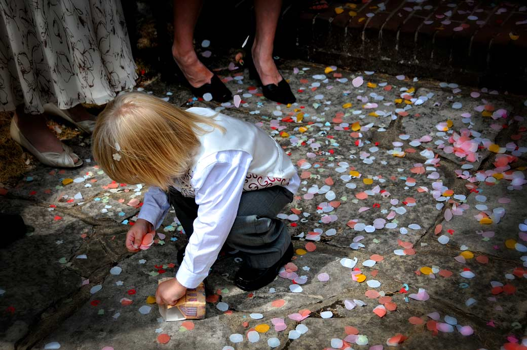 Cute page-boy picking up confetti wedding photograph captured on the steps of Weybridge Register Office a wedding venue in Surrey