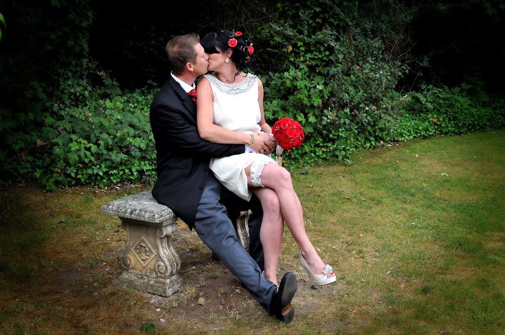 Passionate Bride and Groom sitting down kissing wedding picture at Weybridge Register Office captured by Surrey Lane wedding photography
