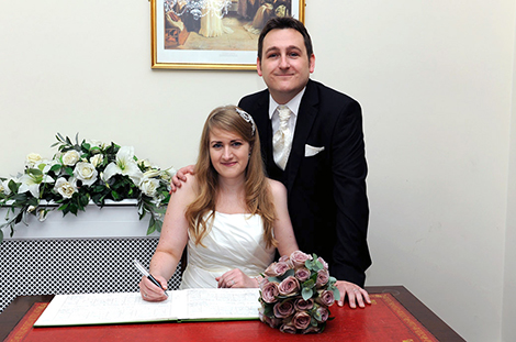 Happy newlywed couple signing the Marriage Register in this sweet Rylston Suite wedding photograph taken in Surrey wedding venue Weybridge Register Office