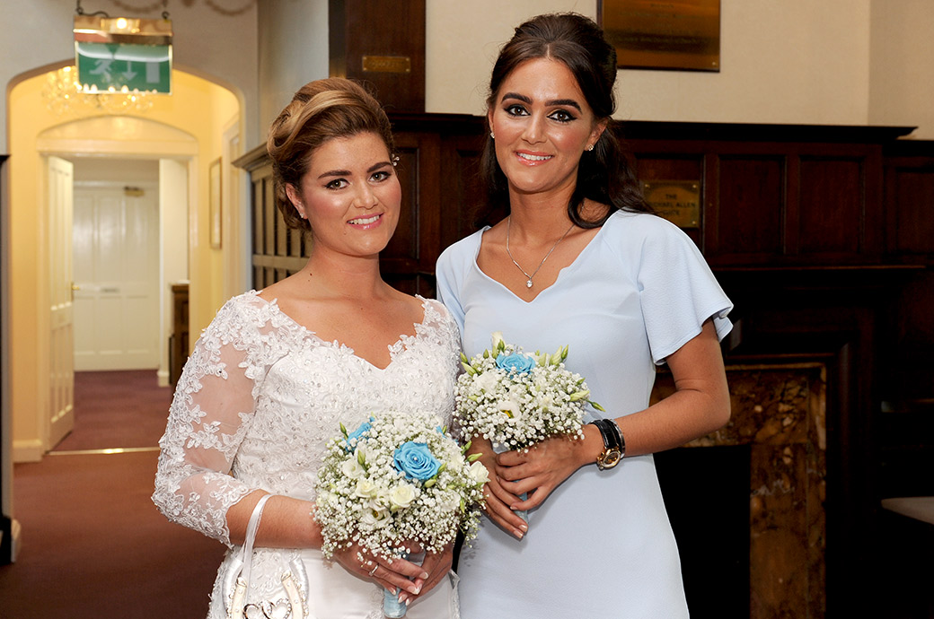 Lovely smiling Bride poses with her Matron of Honor before entering the Rylston Suite at Surrey wedding venue Weybridge Register Office for her marriage