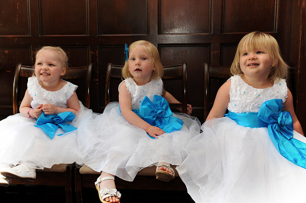 Three Cute little blonde bridesmaids wearing white dresses and bight blue sashes captured at Weybridge Register Office in Surrey as they sit outside the Rylston Suite
