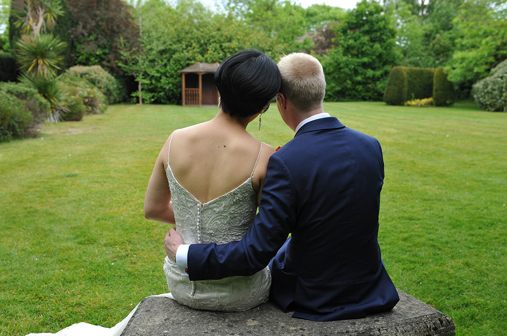 Romantic Bride and groom in the garden at popular wedding venue Weybridge Register Office Surrey sit on a bench arms around each other and heads resting on each others