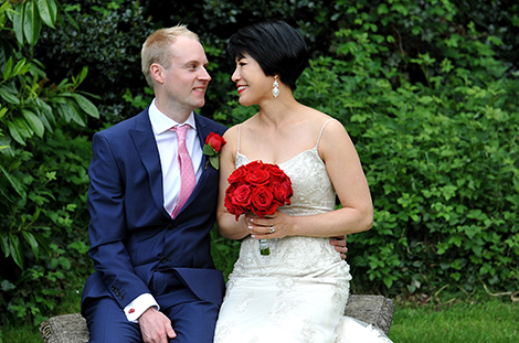 Smiles and loving looks as the happy newlyweds sit on the stone bench in the large garden at the Weybridge Register Office in Surrey