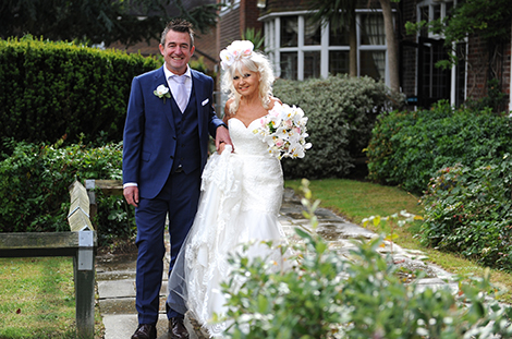 All smiles as they happy newlywed couple stand in the garden at Surrey wedding venue Weybridge Register Office after their marriage in the Rylston Suite