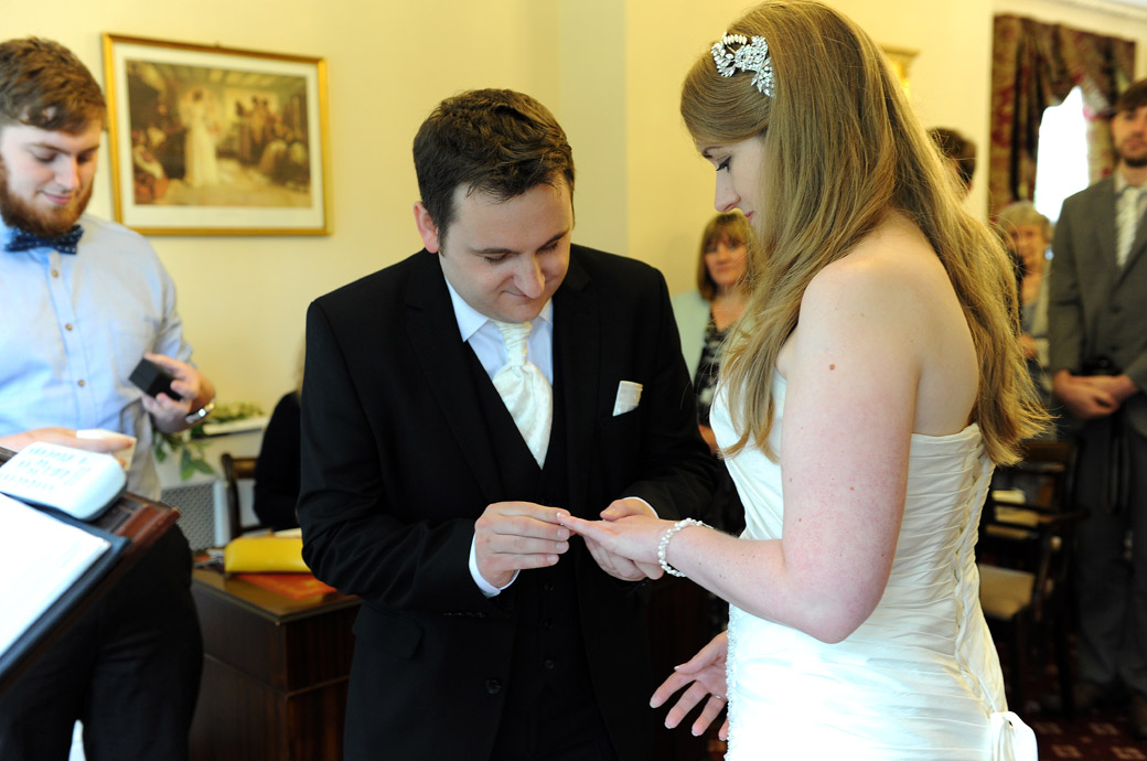 That part of the marriage ceremony where the Groom places the wedding ring onto his Bride's finger in this delicate Weybridge Register Office wedding photo