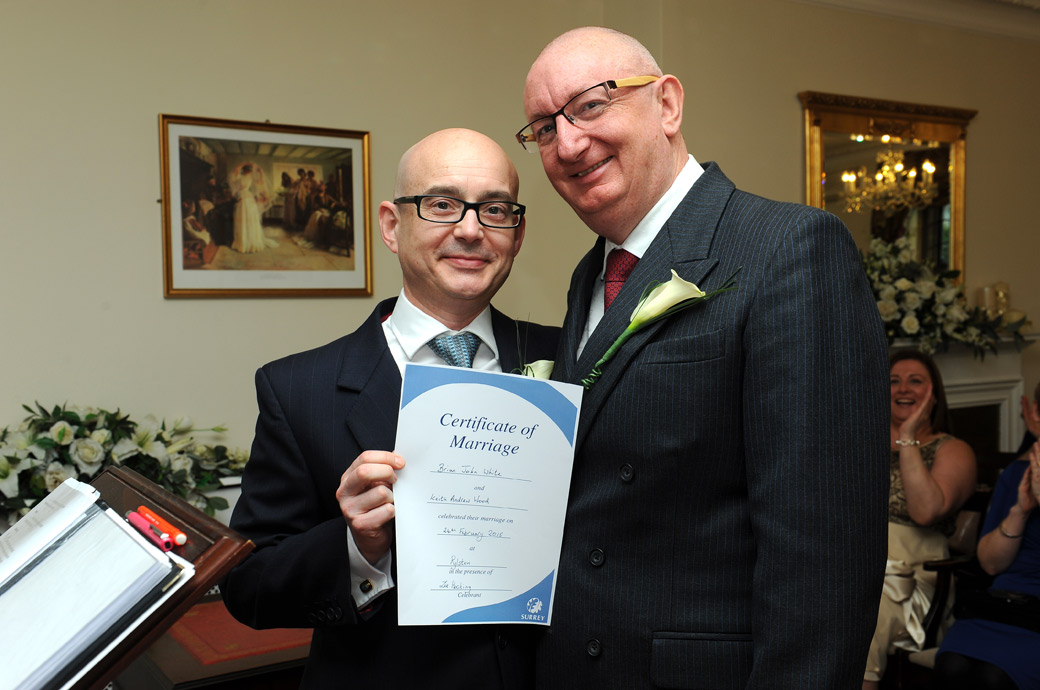 The happy Grooms captured in this wedding picture in the Rylston Suite at Surrey wedding venue Weybridge Register Office as they proudly pose with their marriage certificate