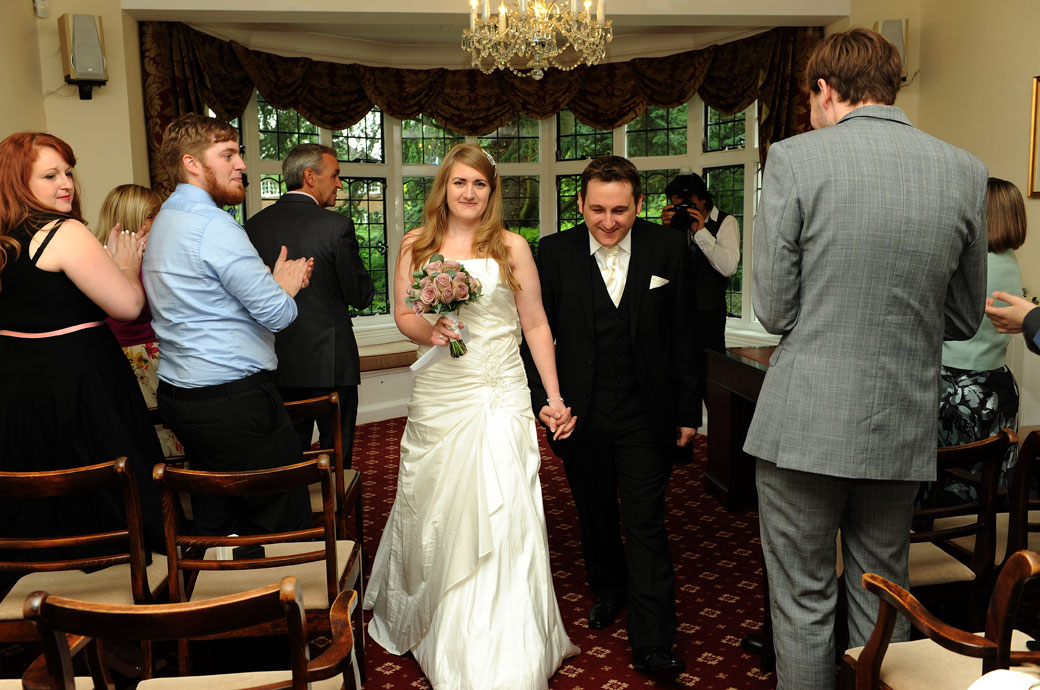 Smiling Bride and groom at Surrey wedding venue Weybridge Register Office captured in this wedding picture as they walk down the aisle in the Ryston Suite as husband and wife