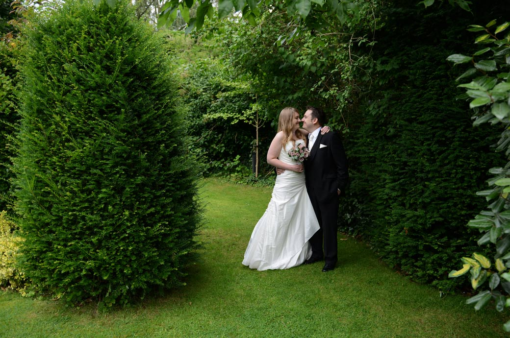 Precious romantic moment for a newlywed couple as they embrace in the garden in this Weybridge Register Office wedding photo captured in this popular Surrey wedding venue