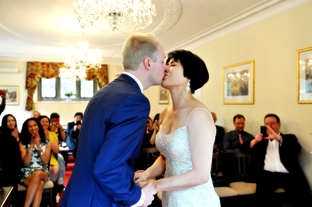 Bride and Groom celebrate their marriage as they hold hands and kiss in this delightful wedding photo taken in Weybridge Register Office Surrey in the Rylston Suite