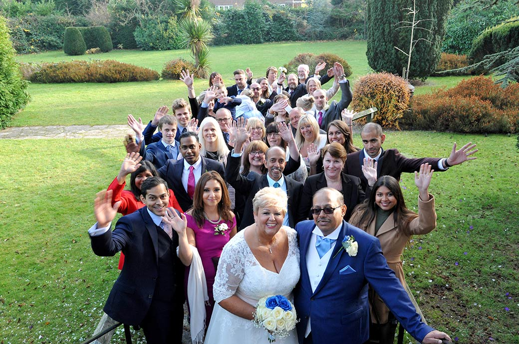 Bride and groom at Surrey wedding venue Weybridge Register Office share the happy moment with their guests as they all wave to the photographer from the garden steps