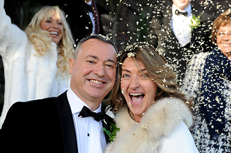 Happy newlywed couple captured at the ever popular Surrey wedding venue Weybridge Register Office enjoying getting covered in confetti on the garden steps