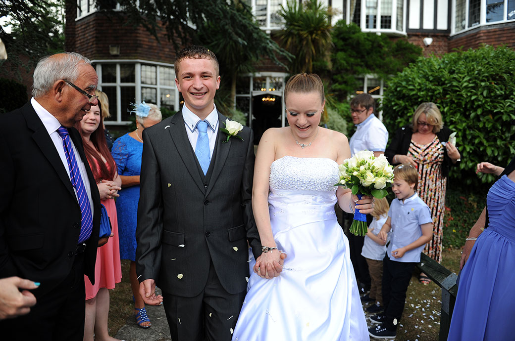 The young newlywed couple in the garden at  Weybridge Register Office in Surrey enjoying themselves as they walk along the path during the confetti throwing