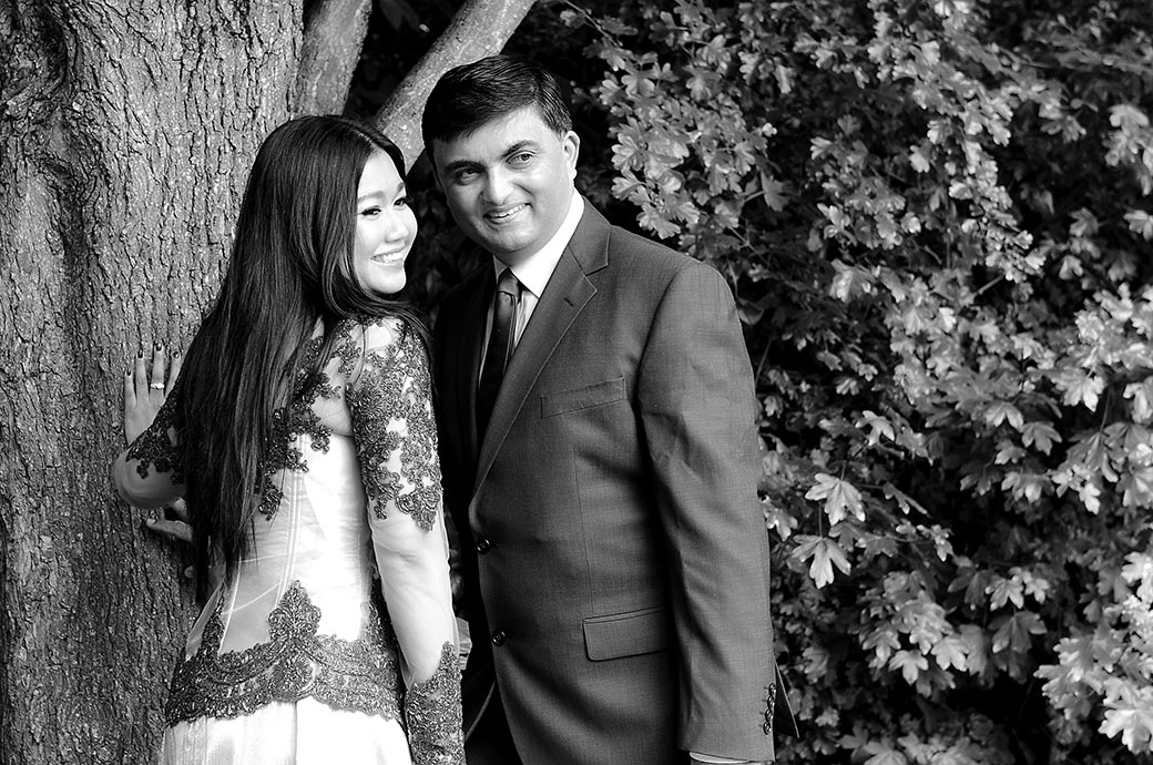 Excited Bride and groom posing by a tree in the wedding picture taken before they depart for the popular Surrey venue Weybridge Register Office to get married