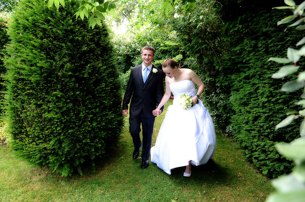 A young Groom holds his young Bride's hand at the Weybridge Register Office wedding venue in Surrey as they walk on the lawn past the mature garden shrubs
