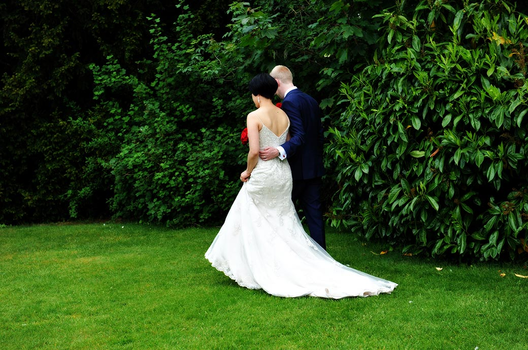 A romantic wedding picture of a Groom delicately holding his wife at  Surrey wedding venue Weybridge Register Office as they walk across the lawn of the mature garden