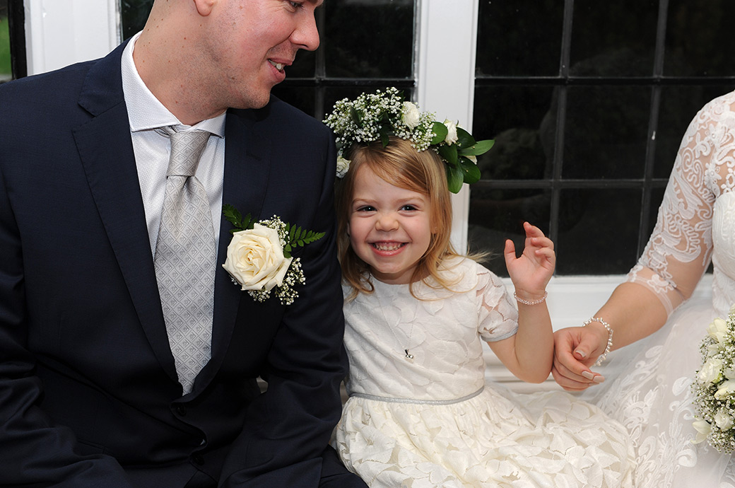 Lovely sweet little girl shows her excitement as she sits with her mum and dad after their marriage in the Rylston Suite at Surrey wedding venue Weybridge Register Office
