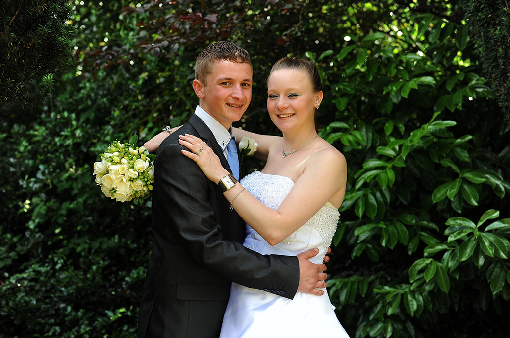 All smiles for the sweet young newlyweds as they relax for a wedding portrait out in the garden at Weybridge Register Office in green and leafy Surrey