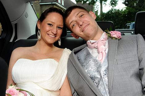 Lovely happy wedding photo of the excited Bride and Groom captured at Surrey wedding venue Weybridge Register Office as they sit in the back of the car as husband and wife