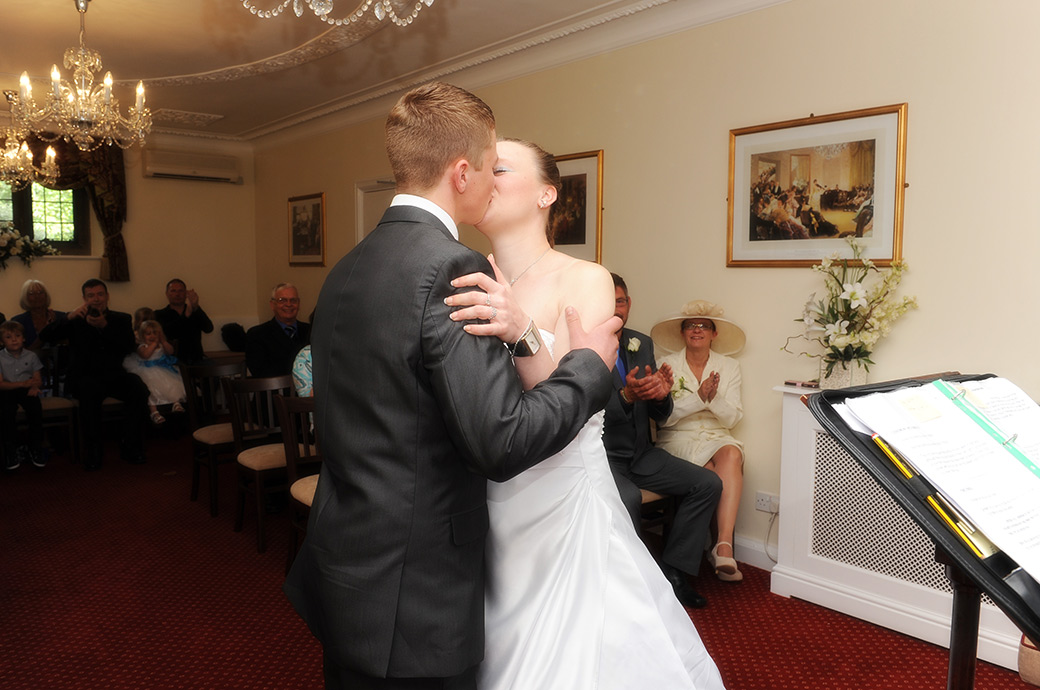 Young Bride and groom's passionate kiss after they are announced husband and wife in the Rylston Suite at wedding venue Weybridge Register Office in Surrey