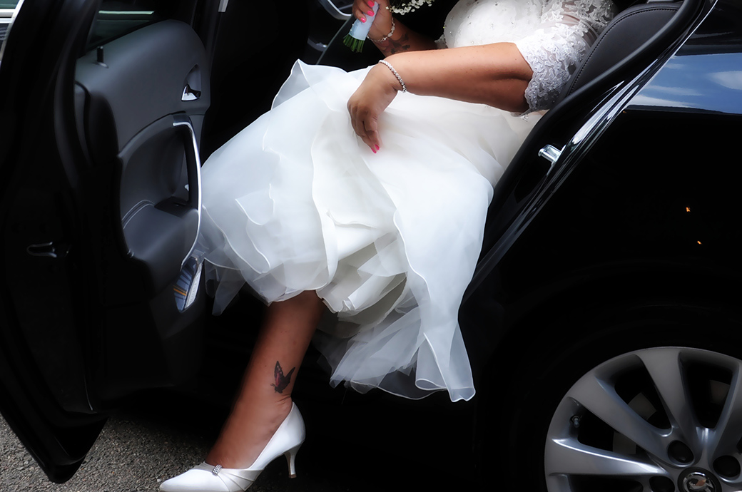 Flash of the Bride's ankle with a butterfly tattoo captured outside Surrey wedding venue Weybridge Register Office as she exist the wedding car