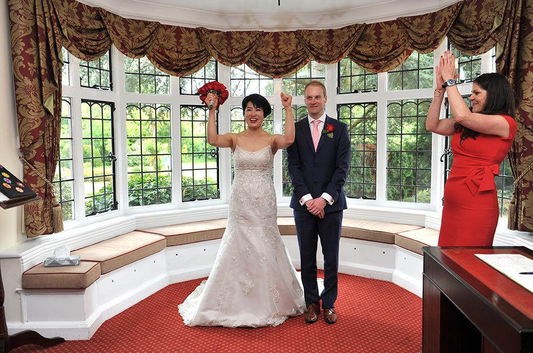 Bride raises her hand and bouquet and cheers as everyone claps in celebration of their Weybridge Register Office wedding in leafy and green Surrey