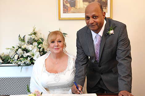 Smiling newlywed couple sign the marriage register after their wedding ceremony in the intimate Rylston Suite at Weybridge Register Office Surrey