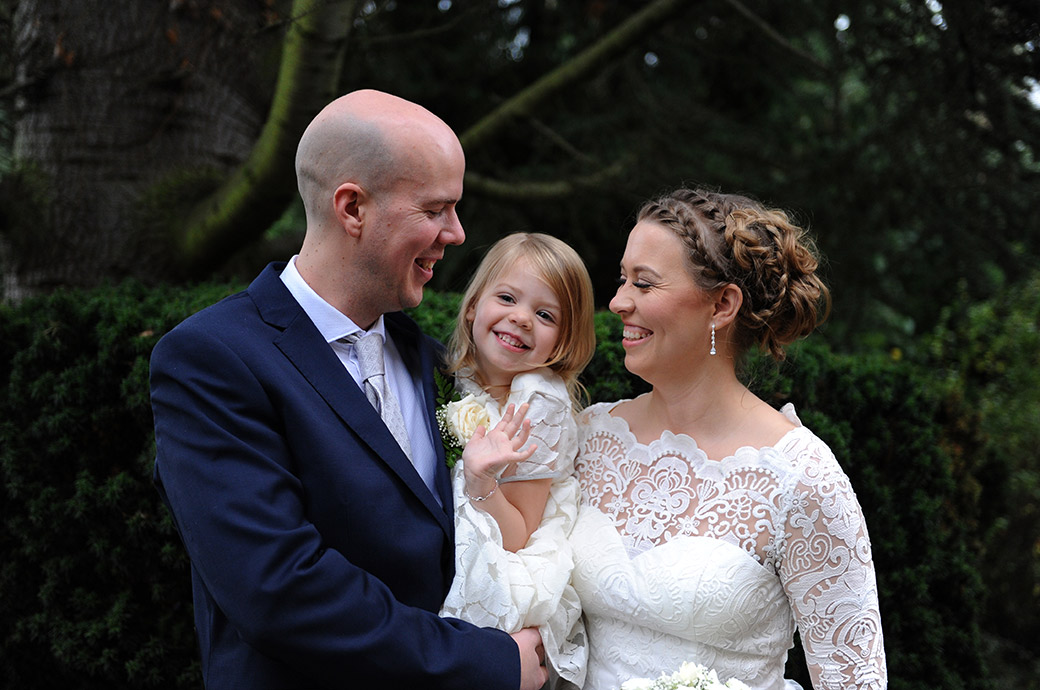Happy smiling daughter pictured at Surrey wedding venue Weybridge Register Office in her dad's arms and with her mum out on the patio after the marriage ceremony