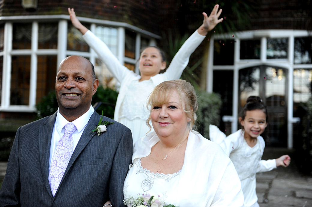 Children have fun as they jump up with their wedding confetti behind their grand parent Bride and Groom out on the garden steps at Surrey wedding venue Weybridge Register Office