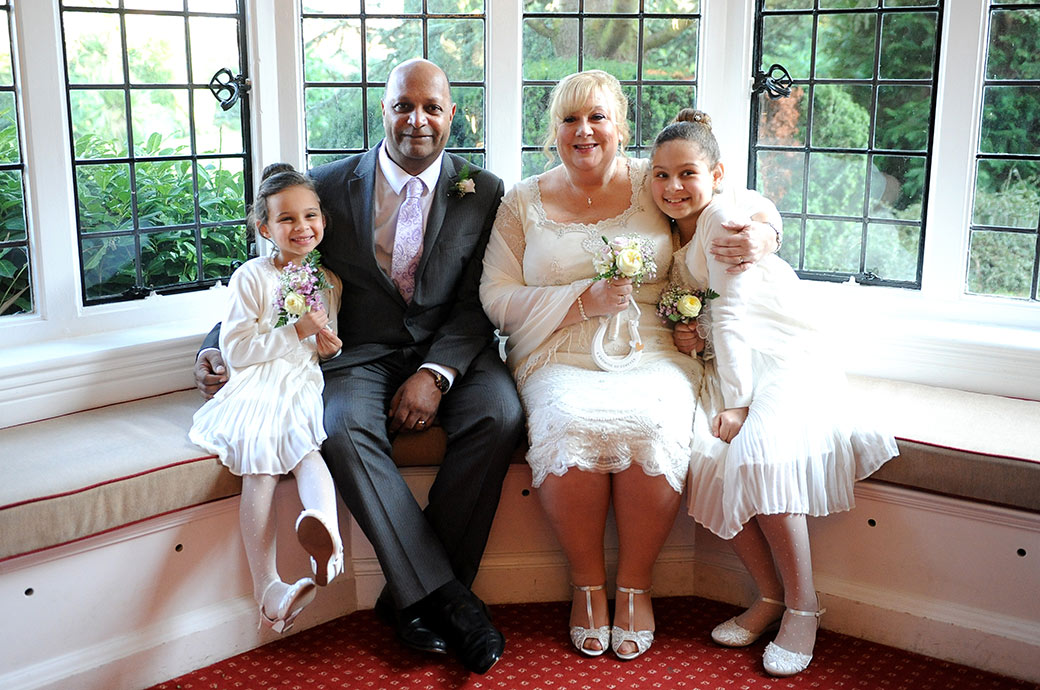 Proud smiling Bride and Groom sharing a moment with their grandchildren after getting married in the Rylston Suite at Weybridge Register Office Surrey