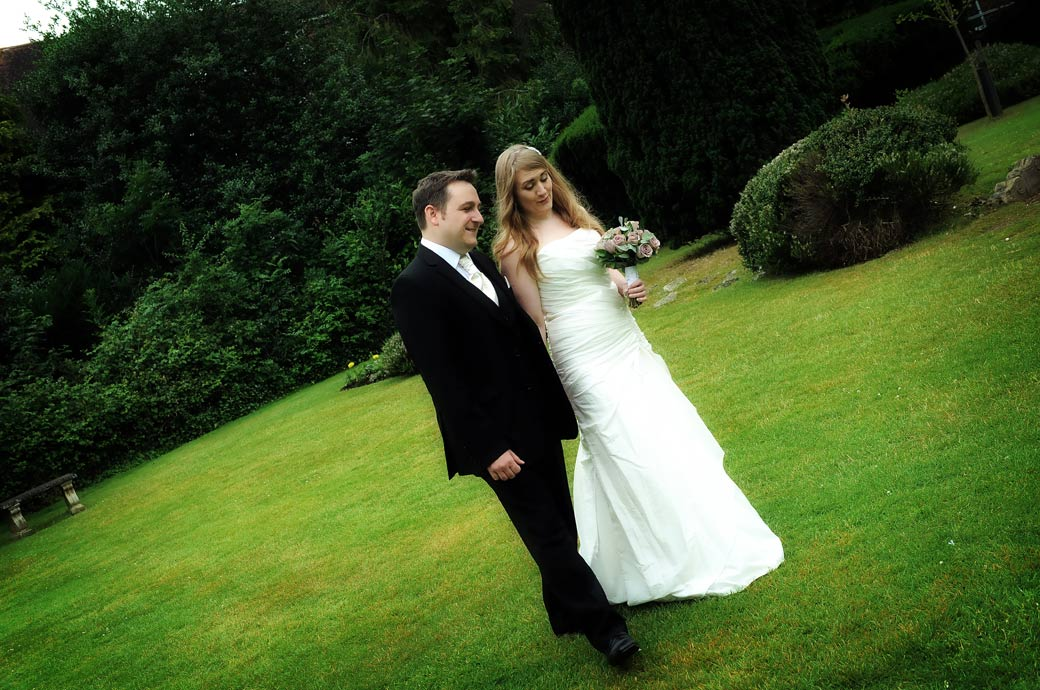 A moment for the newlwed couple captured in this wedding picture as they have a walk and chat on the lawn at Surrey wedding venue Weybridge Register Office