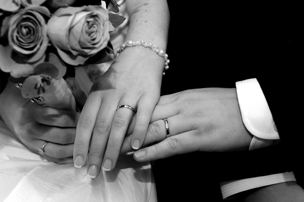 Bride and Groom put their hands together to show off their wedding rings in the Ryston Suite captured at Weybridge Register Office by Surrey Lane wedding photographers