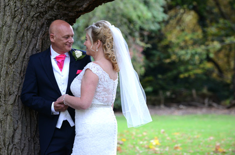 Bride and Groom at Surrey wedding venue Woodlands Park Hotel in a wedding picture holding hands and looking lovingly at each other under a tree in the tranquil grounds