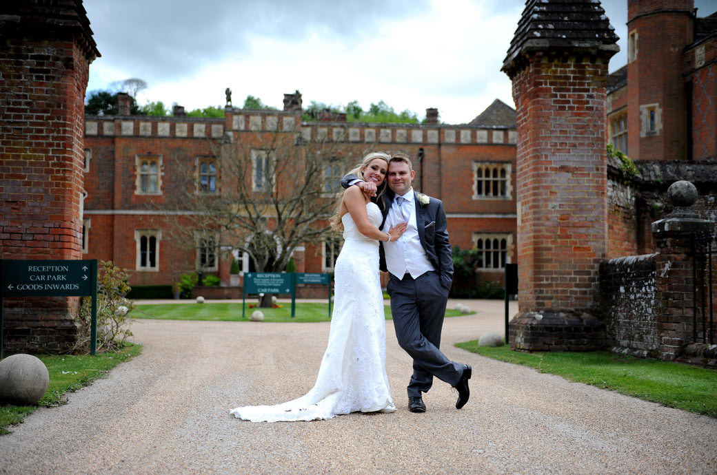 Relaxed happy and married newlyweds stand on the long drive in front of the impressive Surrey wedding venue Wotton House with its origins dating to the 17th century